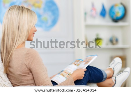 Time to rest. Pleasant beautiful content girl sitting in the armchair half turned while reading magazine - stock photo