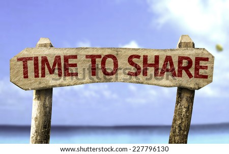 Time to Share wooden sign with a beach on background - stock photo