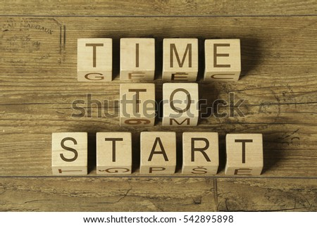 time to start text on wooden cubes on wooden background