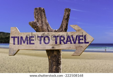 Time to Travel wooden sign with a beach on background - stock photo