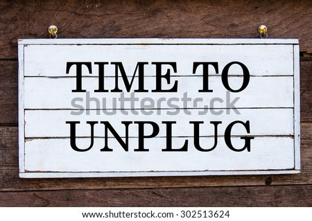 Time To Unplug Inspirational message written on vintage wooden board. Motivation concept image