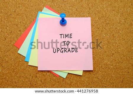 TIME TO UPGRADE written on color sticker notes over cork board background.