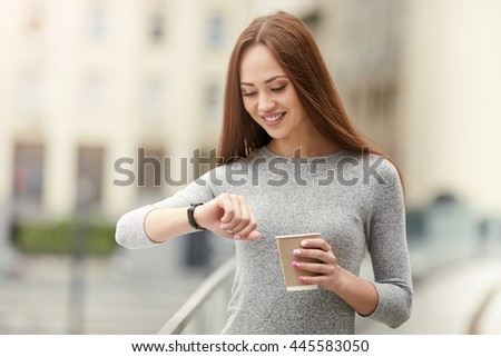 Time to work! Beautiful young woman holding paper cup and looking for wrist watch. Business concept. - stock photo