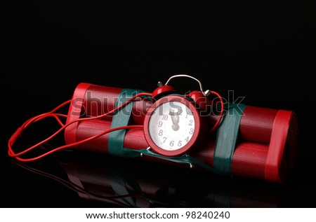 Timebomb made of dynamite isolated on black - stock photo