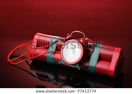 Timebomb made of dynamite on red background - stock photo