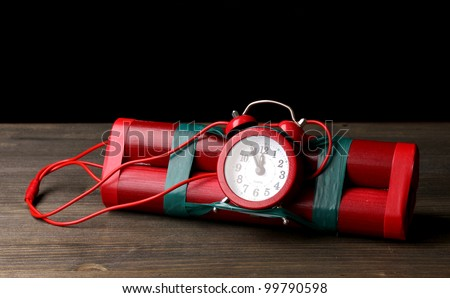 Timebomb made of dynamite on wooden table on black background - stock photo