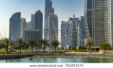 Timelapse view on skyscrapers at waterfront with palms. Residential buildings in Jumeirah Lake Towers reflected in water in Dubai, UAE.  The JLT is a large development which consists of 79 towers wit