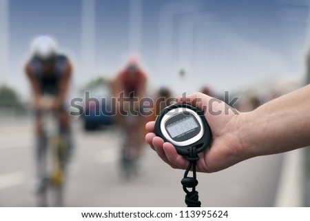 Timing of cyclists in bike race, close-up of hand and clock