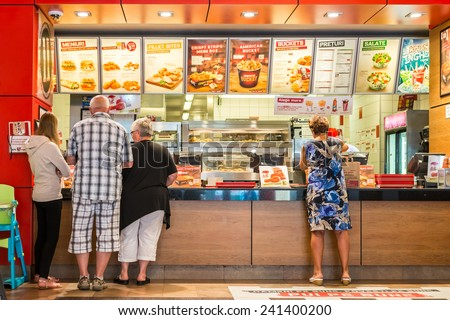 TIMISOARA, ROMANIA - AUGUST 25, 2014: People Order Kentucky Fried Chicken In Fast-Food Restaurant. It is a fast food restaurant chain headquartered in United States specialized in chicken products. - stock photo