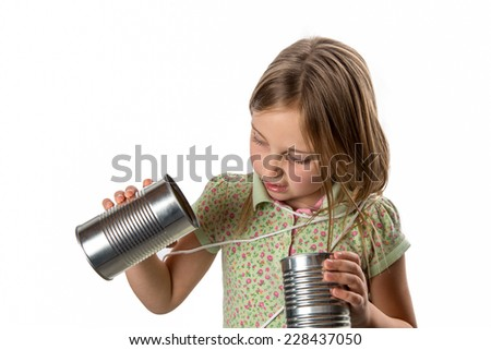 Tin Can Phone - Expressing Skepticism.  Girl tangled up in string from a tin can phone.  Skeptical of this old-school technology.  Close-up portrait.  Isolated on white.  Copy space in upper left. - stock photo
