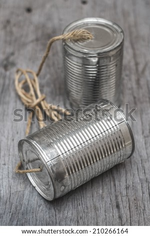 tin can telephone with rope connecting on wooden background - stock photo