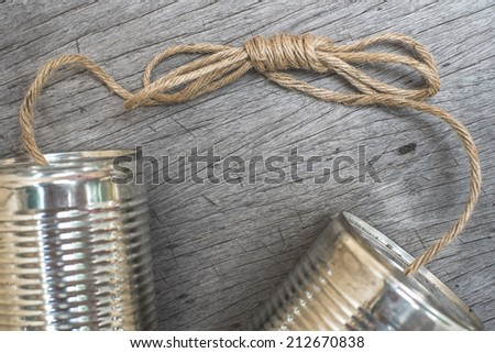 tin cans telephone on wooden background - stock photo