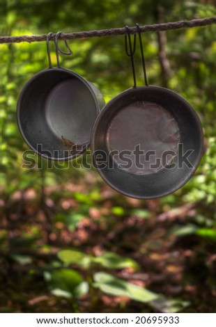 Tin Cups hang on line in woods