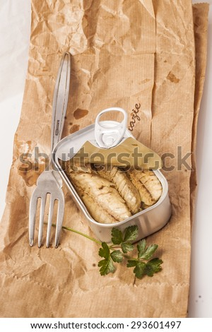 Tin of mackerels placed on a paper bag with fork and parsley.
