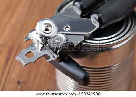 Tin opener opening a can - stock photo