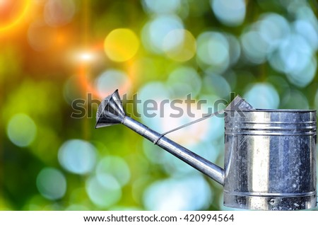 Tin watering can on green nature background