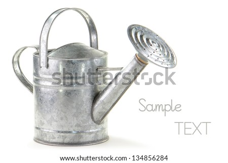 Tin watering can on white background with room for text - stock photo
