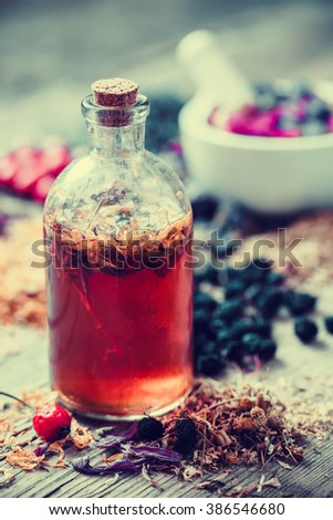 Tincture bottle and mortar of healing herbs on background. Herbal medicine. - stock photo