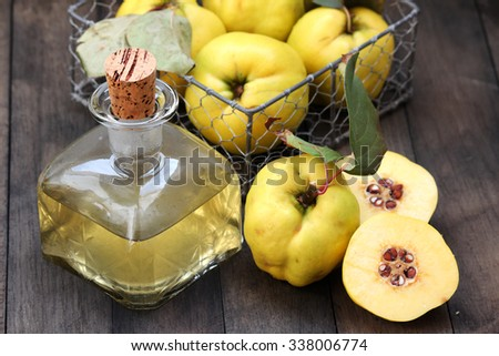 Tincture of quince on a wooden table - stock photo