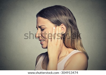 Tinnitus. Closeup side profile sick young woman having ear pain touching her painful head isolated on blue background - stock photo