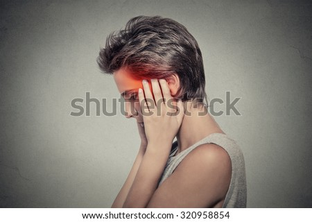 Tinnitus. Closeup up side profile sick female having ear pain headache touching her painful head isolated on gray background. Human face expression  - stock photo