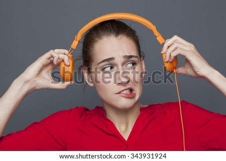 tinnitus headphones concept - dubious 20s girl listening to loud music with earphones on,removing her earphones to avoid nightmare,studio shot - stock photo