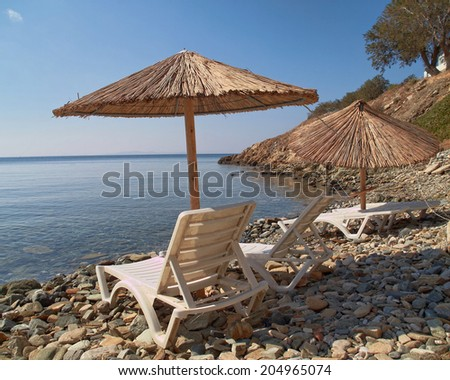 Tinos Greek island, tranquil beach with umbrellas and chairs - stock photo