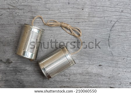 tins telephone with rope connecting on wooden background - stock photo