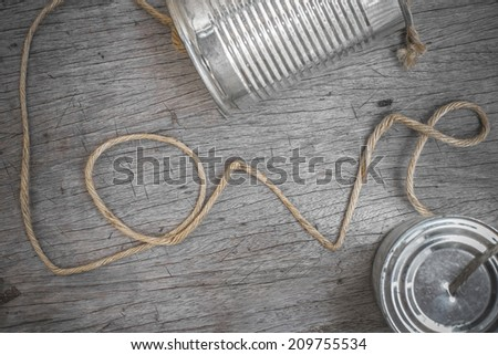 tins telephone with rope connecting shaped the word love on wooden background - stock photo