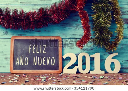 tinsel of different colors and a chalkboard with the text feliz ano nuevo, happy new year in spanish, and white numbers forming the number 2016, on a rustic wooden surface sprinkled with confetti - stock photo