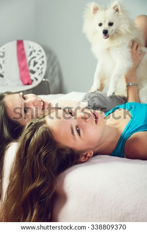 tinted image two girls with a Pomeranian lay on the bed and laughing close-up. vertical format - stock photo