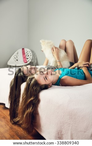 tinted image two girls with a Pomeranian lay on the bed and laughing. vertical format - stock photo