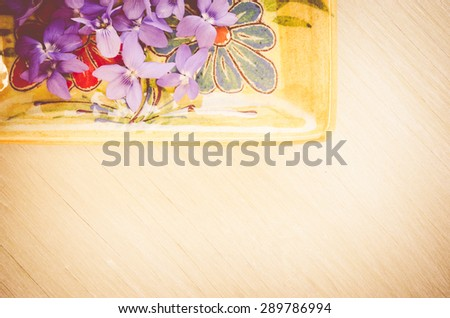 tiny and delicate violets blossoms on a porcelain and bright wood background - stock photo