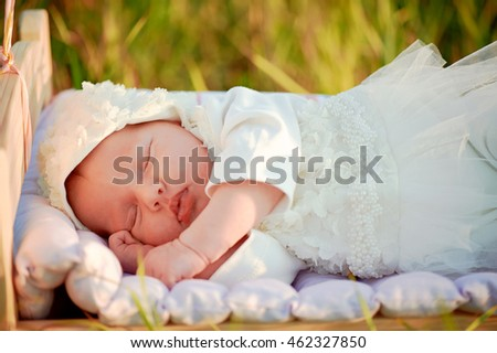 tiny baby asleep in his crib in lace bonnet