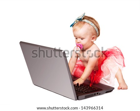 Tiny baby girl working on laptop computer