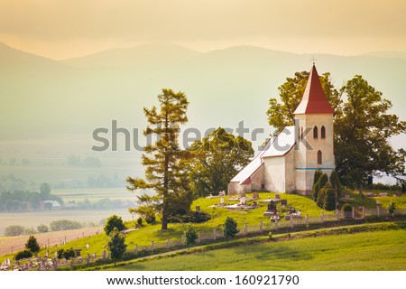 Tiny beautiful small church in Slovakia village with mountain on background - stock photo