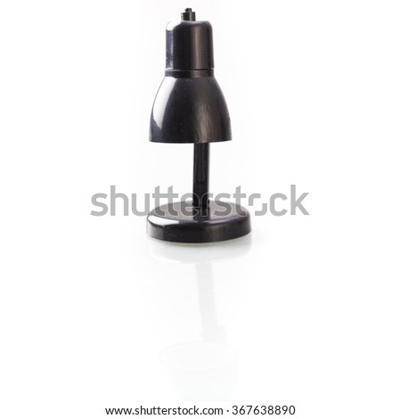 Tiny black lamp on stand, isolated on white background with reflection.