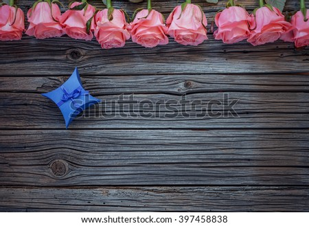 Tiny blue diamond shaped bowed gift box over worn out wooden background with roses on top - stock photo
