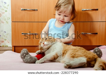 Tiny boy playing with ginger cat house. - stock photo