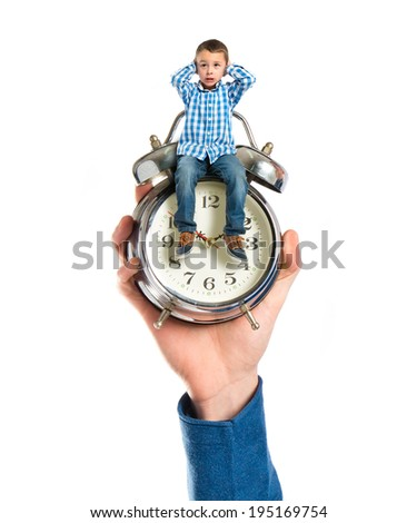 Tiny boy sitting on antique clock covering his ears - stock photo