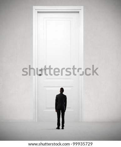 Tiny businessman standing in front of a giant door