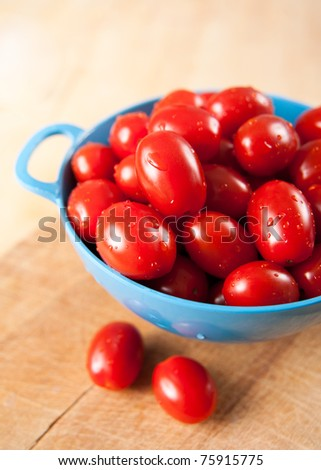 Tiny Cherry Tomatoes Washed in Blue Colander - stock photo