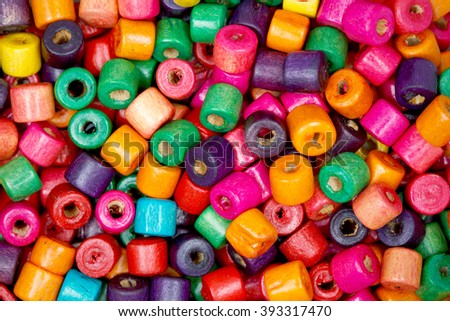 Tiny colored wooden beads closeup.