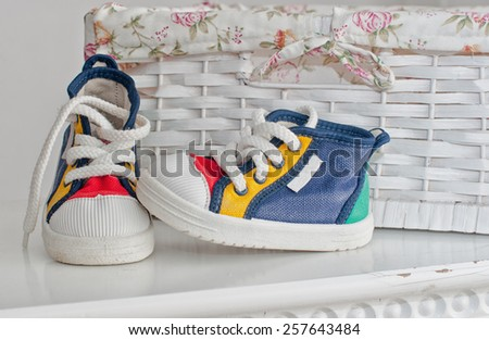 Tiny colorful sneakers on the bedside - stock photo