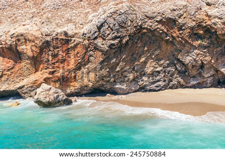 Tiny deserted beach under the cliff - stock photo