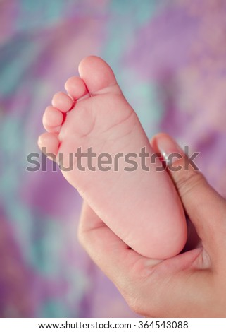 Tiny foot of baby in mother's hand. Sweet babies.  - stock photo
