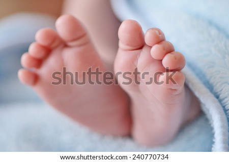 tiny foot of newborn baby in soft selective focus - stock photo