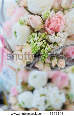Tiny green buds hang from a basket with flowers - stock photo