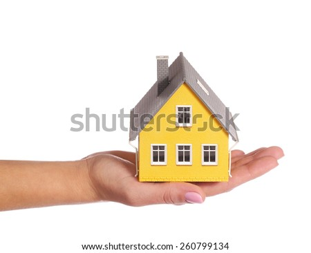 Tiny house in female hand isolated on white - stock photo