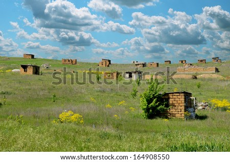 tiny huts in the field. unfinished houses, occupying territory - stock photo